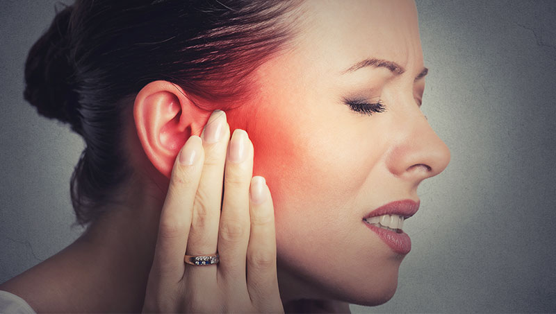 Woman suffering with inner ear pain
